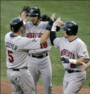 Minnesota's Michael Cuddyer, left, Jason Bartlett, center, and Nick Punto celebrate after scoring on a three-run double by Justin Morneau. The Twins defeated the Royals, 8-5 in 10 innings, Friday night in Kansas City, Mo.