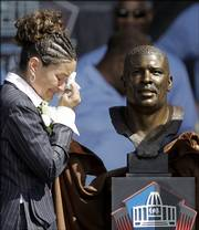Sara White, wife of the late Reggie White, weeps after unveiling the bronze bust of Reggie White during the enshrinement ceremony. The event was Saturday at the Pro Football Hall of Fame in Canton, Ohio.