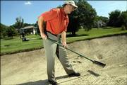 Dick Stuntz, general manager of Alvamar golf course, demonstrates the proper etiquette for raking a sand bunker.