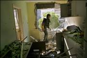 An Israeli policeman searches the kitchen of an apartment Saturday in the northern Israeli town of Kiryat Shmona after it was hit by a Hezbollah rocket. Three Israeli Arab women were killed in one of many attacks as dozens of Hezbollah rockets slammed into communities across northern Israel.