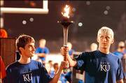 Drew Miller, Iola, at left, and Richie Wagstaff, Prairie Village, pass the torch during Traditions Night 2005 in Memorial Stadium. Both are fifth-generation Jayhawks. This year's Traditions Night will be from 8 p.m. to 9 p.m. Monday, when students will learn Jayhawk songs, cheers and the alma mater.