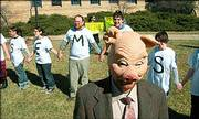 "Brian Azcona, co-president of the Graduate Teaching Assistants Coalition at Kansas University, wears a mask to portray a ""KU bureaucrat"" as GTAs and supporters rally outside of Strong Hall on the Kansas University campus in this Feb. 14 file photo."