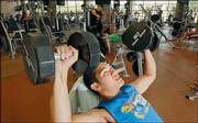 Kansas University junior Steven Le, Wichita, works out with dumbbells at the Student Recreation Fitness Center. Le says he tries to exercise at the gym at least three times a week to stay in shape.