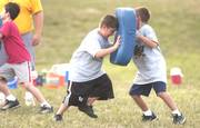 Fouth-graders Jake Holiday, left, and Trip Wright go through a tackle drill during the Lawrence Youth Football practice for the Hurricanes at Dad Perry Park.