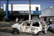 A burned car remains in front of a bank that was attacked Monday in Sao Paulo, Brazil. Assailants sprayed gunfire at police, blew up explosives outside government buildings and torched buses and bank branches Monday in a new wave of attacks.