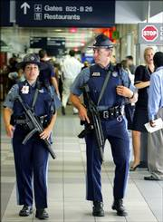 Massachusetts State police patrol with automatic weapons inside a terminal at Logan International Airport in Boston, Thursday, Aug. 10, 2006. The response to the terrorist threat announced Thursday produced long lines at airports as security officials scrambled to put new measures in place and passengers faced perplexing new restrictions, including a ban on carrying liquids onto aircraft.