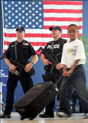 A traveler passes in front of police officers with automatic weapons at JFK International Airport in New York. U.S. passengers are facing heightened security at airports after authorities in London uncovered a terror plot aimed at airlines traveling from Britain to the U.S. Security screening lines grew long and slow-moving as passengers got special inspections, and drinks and most other liquids and gels were banned as carry-on items.