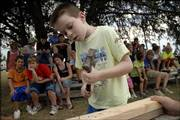 Levi Smith, 8, races against the clock to hammer three nails into a piece of wood during the Old-Time Farm Skills Contest at the Vinland Fair. Thursday was the first day of the 99th fair in Vinland, which is southeast of Lawrence. The fair continues through Saturday.