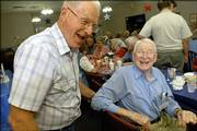 Korean War veteran Ralph Fine, 78, Junction City, left, laughs as he greets his old company commander Harold Woods, Emporia, during a reunion of Korean War veterans of the 439th Engineer Battalion on Friday night at American Legion Dorsey-Liberty Post No. 14, 3408 W. Sixth St.