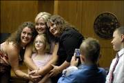 Ciara Ross, 7, gathers with her aunts, from left, Samantha Fabbri, Heather Ross and April Russell at Douglas County District Court for friends and family to snap photographs. Ciara was officially adopted by Heather Ross on Friday at the court. Ciara's father, Thomas E. Murray, was convicted in the November 2003 killing of her mother, Carmin Ross.
