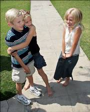Joshua Elin, 9, meets his donor siblings, Cheyenne Jorgenson, 8, left, as Allyson Cross, 7, looks on during his arrival to their reunion June 25 in Fresno, Calif. All three children were conceived from the same sperm donor and their mothers located each other through the Donor Sibling Registry Web site.