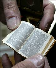Gene S. Albert Jr. displays a Bryce Bible, the smallest printed Bible, at the Christian Heritage Museum.