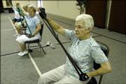 Margaret Jones, front, and Rachel Purvis volunteer with their husbands to help senior citizens stay in shape by teaching exercise classes twice each week at First Baptist Church, 1330 Iowa St. The rubberbands they use provide resistance training like weights.