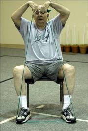 Frank Purvis stretches at First Baptist Church, 1330 Kasold Drive, during a Personal Actions to Health class. Purvis, his wife, Rachel, and Harold and Margaret Jones lead the exercise classes for senior citizens twice each week.