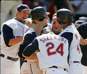 Cleveland Indians players Aaron Boone, left, Ryan Garko, back, Grady Sizemore (24) and Victor Martinez, right, congratulate Travis Hafner after his ninth-inning, two-out single off Jimmy Gobble gave the Indians a 5-4 win in game one of a doubleheader Saturday in Cleveland.