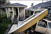 A boat rests partially on a car July 24 in the Lower Ninth Ward of New Orleans, where much cleanup remains to be done after the neighborhood was flooded by Hurricane Katrina.