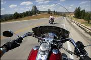 Taylor McKee rides near Wyoming's Devil's Tower as his friend James Potter is seen through the windshield of his Harley Davidson. They and a group of other Kansas Citians were attending the 2006 Sturgis Motorcycle Rally Thursday near Sturgis, S.D.