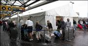 A line of Passengers snakes through a tent at London's Gatwick Airport North Terminal. On Sunday, flights continued to be delayed and some canceled due to extra security measures imposed after a foiled terror plot to blow up airplanes.