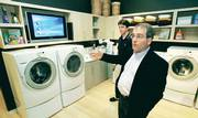 Jonathan Cluts, director of consumer prototyping and strategy at Microsoft Corp., discusses Microsoft's involvement in the Laundry Time project at the Whirlpool Corp.'s Insperience Studio in Atlanta. The project hooks a Whirlpool Duet Sport washer dryer to a Microsoft-programmed computer, a Panasonic TV screen, and a cell phone to allow the consumer to keep up with their laundry remotely. In background, Colson Nunnelley demonstrates remote features. 