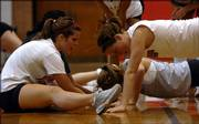 Lawrence High senior Maddie Fisher, left, motivates teammate Emily Renfro. Renfro worked through a round of pushups Monday afternoon during the first day of volleyball practice at the school gymnasium.