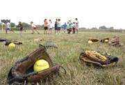 Baseball gloves lay scattered in the outfield at girls are split up into groups during tryouts for the Phenix youth girls softball team on Saturday at Haskell softball field.