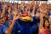 "Baby Jay is nearly swallowed up by freshmen learning to ""wave the wheat"" during Kansas University&squot;s Traditions Night at Memorial Stadium. Freshmen who attended the event Monday also learned about KU&squot;s alma mater, fight songs and folklore. For more photos, see page 5B."