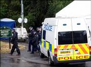 British police leave their temporary headquarters on the edge of King's Wood in High Wycombe, England, about 35 miles west of London. London's anti-terrorist police pressed ahead with a major search in the woodland area on Monday. The search will continue through today, though officers declined to say whether anything significant had been discovered.