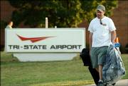 Wayne Bloss, of Huntington, W.Va., carries his suitcases out of the Tri-State Airport in Ceredo, W.Va., after the airport terminal was evacuated Thursday. Bloss missed his flight to Orlando, Fla., earlier in the day and was told he could return later to retrieve his luggage. Two bottles of liquid found in a woman's carry-on luggage twice tested positive for explosives, a Transportation Security Administration spokeswoman said. But later tests found no explosives in the bottles.