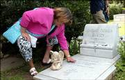 Patsy Ramsey's sister Paulette Davis brushes off the grave of JonBenet Ramsey on Thursday at St. James Episcopal Cemetery in Marietta, Ga. A man arrested in Thailand is being held in connection with JonBenet's 1996 slaying.