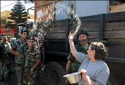 A Lebanese woman throws rice and rose petals at Lebanese soldiers after their arrival Thursday to the southern town of Marjayoun, Lebanon. Lebanese troops, backed by tanks and armored vehicles, have begun deploying south of the Litani River in line with a U.N. cease-fire plan to end fighting between Israel and Hezbollah, a senior military official said Thursday.