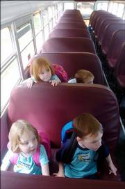Melissa Headrick, front left, and Grant Headrick sit in the front seat of the school bus as their siblings Jaycie, back left, and Sean sit in the seat behind as they wait to ride home after their first day of preschool Thursday.