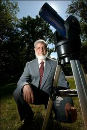 Astronomer Khalid Shaukat poses with a telescope at his home in Silver Spring, Md. He uses astronomical calculations to determine the Islamic calendar, so that all North American Muslims can celebrate holidays on the right day.