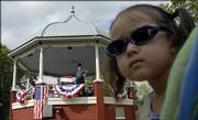Eden Rodriguez, 2, Lawrence, looks back at the audience as Howard Duncan, Lecompton, portrays Kansas Territorial Gov. Charles Robinson Saturday at a South Park gazebo.