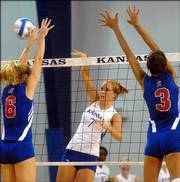 KU alumna Laura Rohde Curry, left tries to block a spike by Kansas University's Emily Brown.