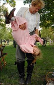 Charles Walthall, of Blue Springs, hangs Kaitlynn McCaully, 6, Leavenworth, upside down after she taunted him to chase her. Sons of the Union Veterans in Lawrence and others re-enacted history Saturday at South Park, with the regional celebration War on the Western Frontier.