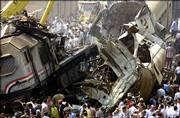 People gather Monday at the site of a train crash in a rail station of Qalyoub, north of Cairo, Egypt. A passenger train barreled into a northern Egypt railway station Monday and collided with a second train, killing 58 people and injuring 142.