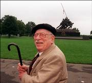 In a file photo with the Iwo Jima Memorial in the background, Pulitzer Prize-winning photographer Joe Rosenthal poses for photographers in 1995 in Arlington, Va., during a ceremony honoring photographers who lost their lives covering military conflicts around the world. Rosenthal won a Pulitzer Prize for making the photo that the Iwo Jima Memorial is modeled after. Rosenthal died Sunday at age 94.