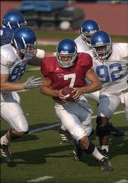 Kansas quarterback Adam Barmann is hounded by KU defenders during a scrimmage. The Jayhawks practiced Wednesday at Memorial Stadium as part of Fan Appreciation Day.