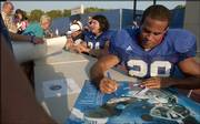 Kansas senior running back Jon Cornish autographs posters and footballs at the end of Fan Appreciation Day. The Jayhawks scrimmaged Wednesday at Memorial Stadium, then mingled on the field with fans.