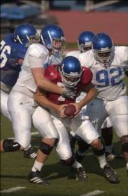 Senior quarterback Adam Barmann is brought down by the Kansas defense during Wednesday&#39;s scrimmage.