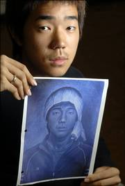 Alex Kim displays a copy of his award-winning self-portrait at Lawrence High School. Kim's picture will be on display along a tunnel that connects the U.S. House of Representatives with the U.S. Capitol in Washington, D.C.