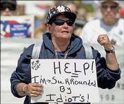 Marge Trowbridge, a lone supporter of President Bush, carries a sign claiming she is surrounded by idiots as she walks in front of an anti-war protest in Kennebunkport, Maine.