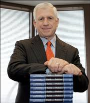 "Former U.S. Sen. John Danforth leans on a stack of his latest book, ""Faith and Politics,"" in his St. Louis office."