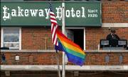 """J.R. Knight plays music, including """"Somewhere Over the Rainbow,"""" from the balcony of the Lakeway Hotel in Meade on Sunday as members of the Topeka-based anti-gay Westboro Baptist Church picket across the street. The church group was in town because the hotel has been flying a rainbow flag, a gift from the 12-year-old son of the owners."""