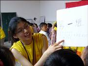 A squad of children works with Jing Li, Free State High School senior, on pronouncing the English alphabet. Tutors with the Hunan University program, called Love in Xiangxi: Big Hands Hold Little Hands, traveled to China's Xiangxi autonomous district this summer to volunteer and relay funds and supplies to the rural area.