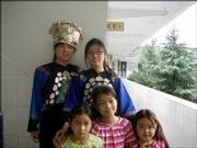 In her free time during her trip to China, Jing Li, top right, tries on traditional Miao clothing with another volunteer from Hunan University. The three young girls in the front row advised them on how to put on the unfamiliar garb.