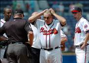 Atlanta Braves manager Bobby Cox, center, speaks to an umpire on the mound while his players look on during a game against the Florida Marlins. Cox finds himself in a strange place this season - looking up at the .500 mark for the first time in more than two decades.