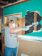 Karin Feltman, emergency room nurse at Lawrence Memorial Hospital, tears down the wall of a home in Long Beach, Miss., which was ravaged by Hurricane Katrina. Feltman helped with cleanup efforts in March. She said the home belonged to a 98-year-old resident whose parents had built it.