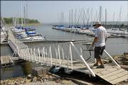 Gary Tempelton, who lives along the west side of Perry Lake, walks down a usually level dock to his sailboat. The U.S. Army Corps of Engineers has been releasing water from the lake to the Missouri River, lowering the lake level.