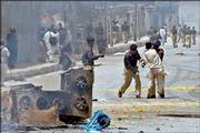 Police officers beat a protester during a clash in Quetta, Pakistan. Gunfire and rioting broke out Tuesday for a fourth straight day after an emotion-charged funeral service for a prominent tribal chief killed by Pakistani forces. Two police were wounded and dozens of shops destroyed in the violence.